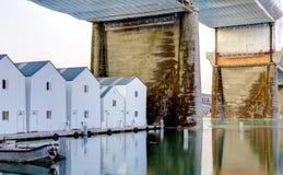 White boat houses under large bridge. Tacoma, downtown. Royalty Free Stock Image