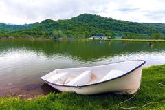 White boat on the lake shore, Sochi, Russia. A boat without oars tied with a rope is on the green grass in front of the pond on the background of the Royalty Free Stock Images