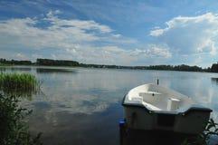 White boat on the lake shore. White wooden boat on the lake shore Stock Image