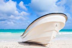 White boat lays on sandy beach, ocean coast Stock Photo
