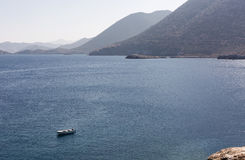 White boat on moorage at smooth sea surface against mountains background.  Royalty Free Stock Images