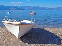 White boat on Nikolaiika Beach and the Corinthian Gulf, Greece. A white boat sits on Nikolaika Beach near the blue waters of the Corinthian Gulf on the Royalty Free Stock Images