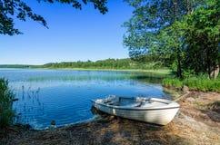 White boat on Norwegian lake coast Royalty Free Stock Photos