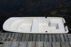 The white boat is tied in the dock. This white boat is the only one tied upat thispier royalty free stock image