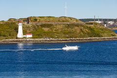 White Boat Past White Lighthouse stock photo