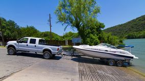 A white boat and a white pickup truck preparing to lauch. AUSTIN, TEXAS - MAY 19 2014: preparing to launch a motorboat from a trailer Stock Image