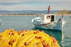 White boat and pile of yellow fishing nets in port Royalty Free Stock Photo