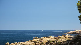White boat on a quiet Mediterranean rock shore Stock Images