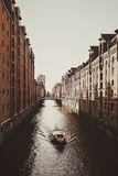 White Boat on River in Between Brown Concrete Buildings during Daytime Royalty Free Stock Photos