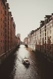 White Boat on River in Between Brown Concrete Buildings during Daytime Royalty Free Stock Photography