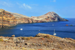 The white boat in a rocky bay Stock Photo