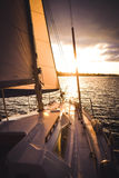 White boat with a sail on the water Stock Photos