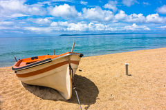 White boat on a sandy beach at morning, west coast of Sithonia Stock Image
