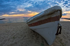White boat on a sandy beach at sunset, west coast of Sithonia Stock Photos