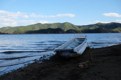 White boat stay on the beach of Lugu lake. In China, Sichuan province, Lugu lake Stock Images