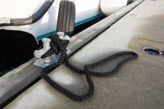 White boat tied to the pier with a black rope royalty free stock images