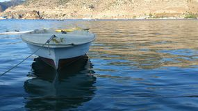White boat. Tied white boat in water of sea in Fethie Turkey with reflection and mountain on background Stock Photo