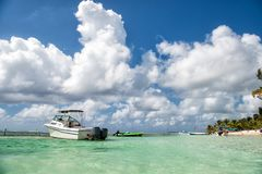 White boat in turquoise sea in Costa Maya, Mexico. White boat in turquoise sea and tropical palm beach under cloudy blue sky background in Costa Maya, Mexico Stock Photography