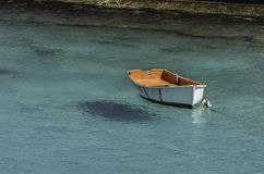 White Boat in Turquoise Sea. White dinghy floating alone in calm turquoise water Stock Image