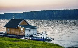 White Boat Beside Wooden House on Water Near Forest Royalty Free Stock Photos