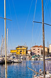 White boats, blue sky and colorful buildings at Piran harbor, Istria Royalty Free Stock Images