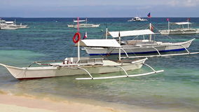 White boats near shore. White sandy beach near the boat stock video footage
