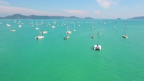 White boats and yachts in clear blue water near pier. HD aerial slowmotion shot. Phuket, Thailand. White boats and yachts in clear blue water near pier. HD stock video footage