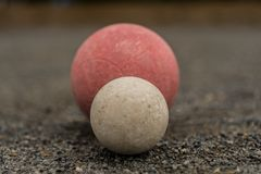 White Bocce Ball with Red Ball Centered. As they rest on a Bocce Ball Court Stock Photos