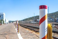 White bollard post with train tracks royalty free stock photography