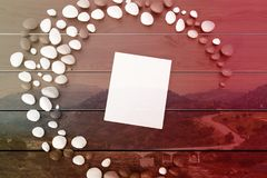White book on a gray table toned. Top view of a white book with a blank cover lying on a gray wooden table inside a crescent made of pebbles. 3d rendering mock Royalty Free Stock Images
