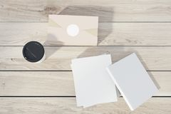 White books, a coffee and a box. Stack of white books lying on a wooden table, a paper cup of coffee and a closed box. Top view. 3d rendering mock up Stock Images