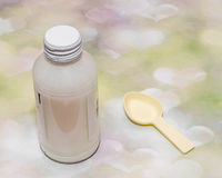 White bottle with medical drug syrup and a small spoon, colored hearts background Royalty Free Stock Photo