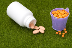 White bottle of orange pills and buckets filled with tablets Royalty Free Stock Photos