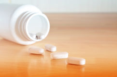 White bottle of pills. Pharmacy theme. White bottle of pills on a wooden surface. Closeup Royalty Free Stock Image