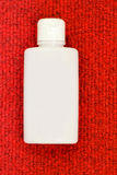 White bottle on red Royalty Free Stock Photography