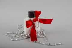 White bottle with a red bow. Bottle and beads stock image