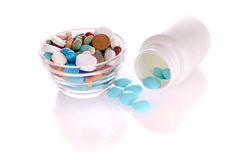 White bottle and saucer with many-colored pills. White bottle with blue tablets and transparent saucer with many-colored pills Royalty Free Stock Photos
