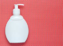 White bottle of shampoo on creative red background in polka dot, top view. stock photo
