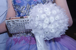 White bouquet of artificial flowers, a bag and a fragment of lilac dresses Stock Photos