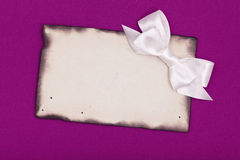 White bow and burnt blank paper Stock Photo