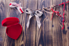 White bow and different ribbons hanging on a rope and open red heart. White bow and different ribbons hanging on a rope and open red box in a shape of heart on a royalty free stock image