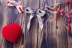 White bow and different ribbons hanging on a rope and red heart. On a wooden background royalty free stock photos