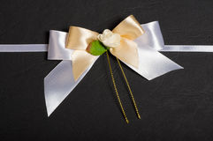 White bow with a flower. White bow with a ribbon and a flower on black textured background Stock Images