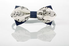 White bow tie with notes on a white background Royalty Free Stock Photos