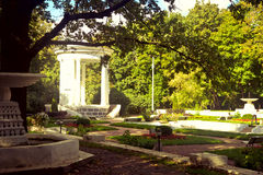 White bower in a park. Beautiful park with antique white bower Stock Image