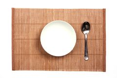 White bowl on a bamboo mat Royalty Free Stock Photos