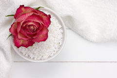 White bowl with bath salt and red rose on top Stock Image