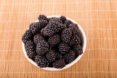 White Bowl of Blackberries on Bamboo Mat Stock Photo