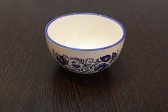 White bowl with blue flowers. On a dark table royalty free stock photo