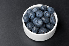 White bowl with blueberries on a black background, top view Stock Images
